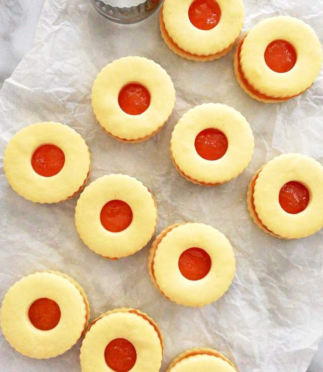 apricot jam filled sandwich cookies laid out on parchment paper close up overhead image