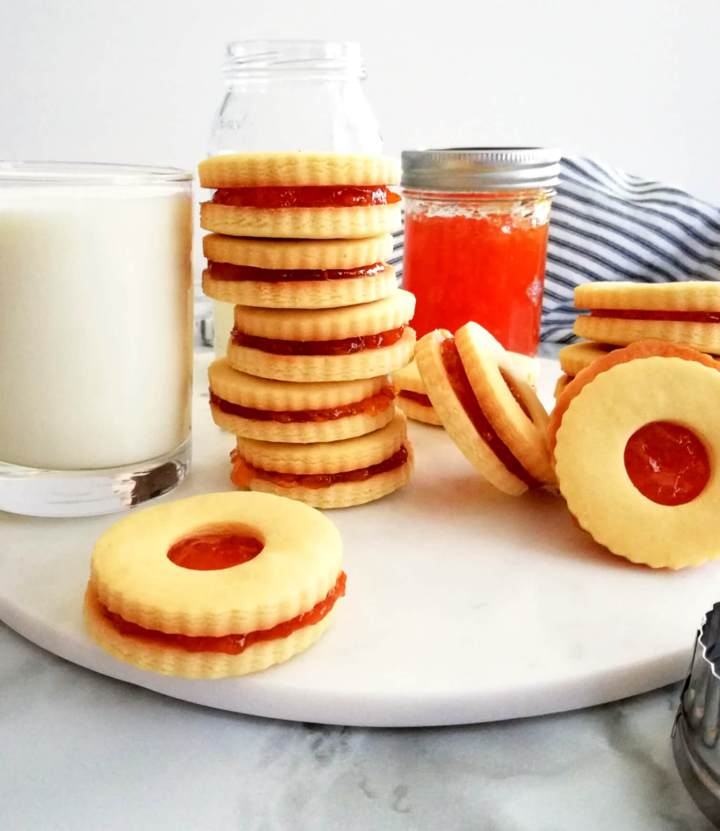 apricot jam filled sandwich cookies on serving board