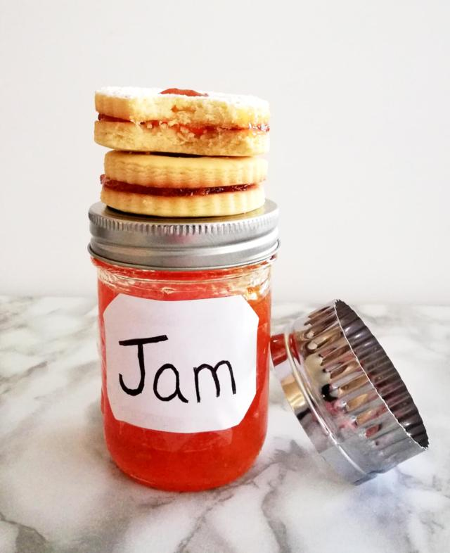 apricot jam filled sandwich cookies stacked on top of jar of jam