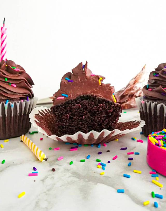 chocolate cupcakes frosted and topped with sprinkles cupcake sliced in half head on image