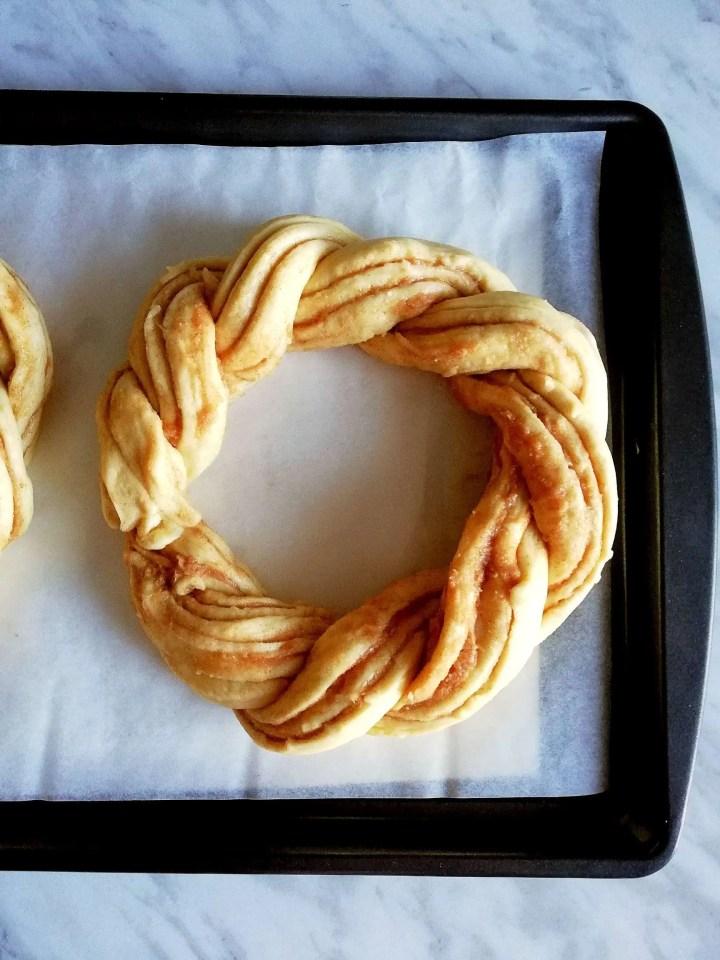 cinnamon swirl wreath bread shaped on baking sheet