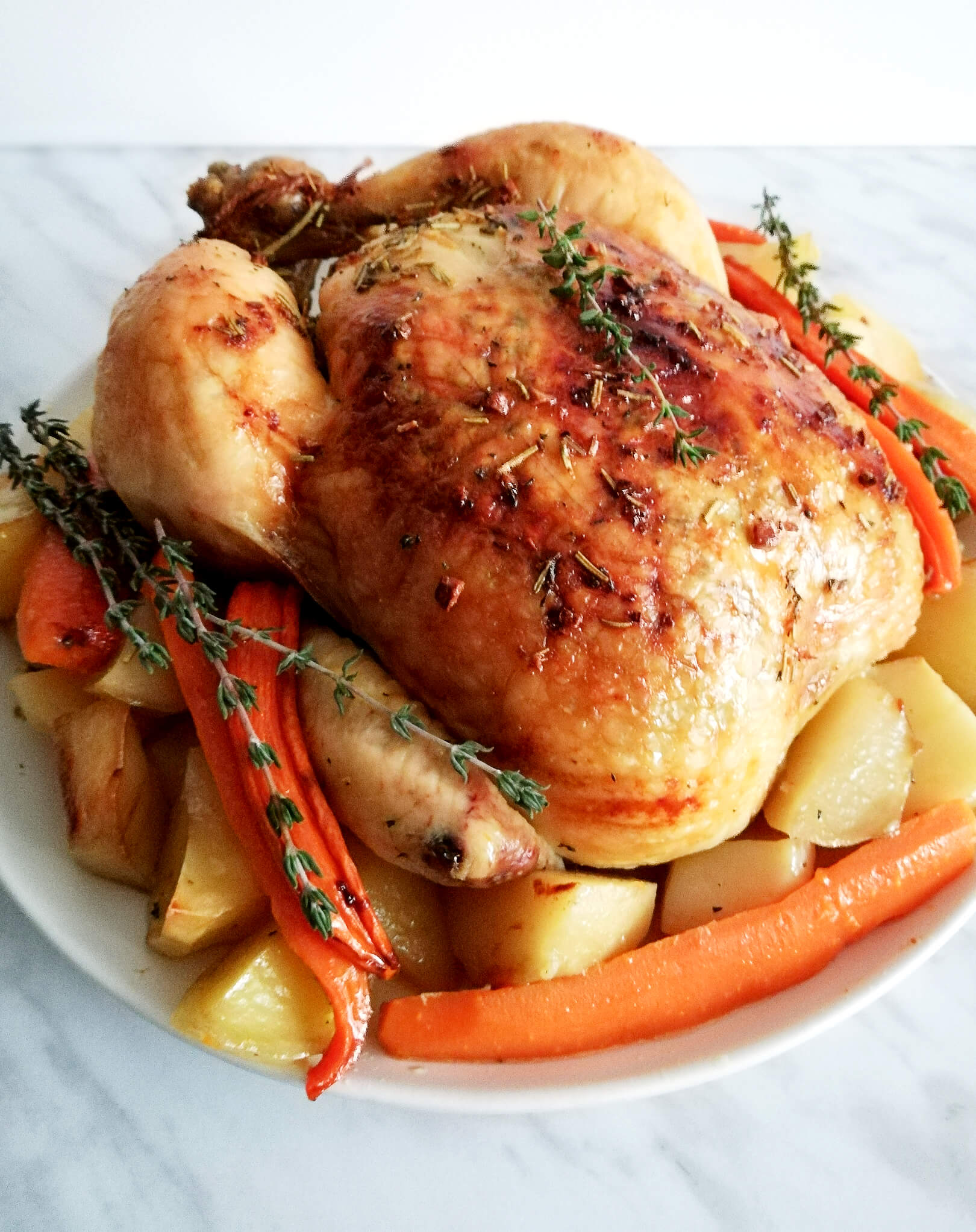 herb roasted chicken with potatoes and carrots side view zoomed in