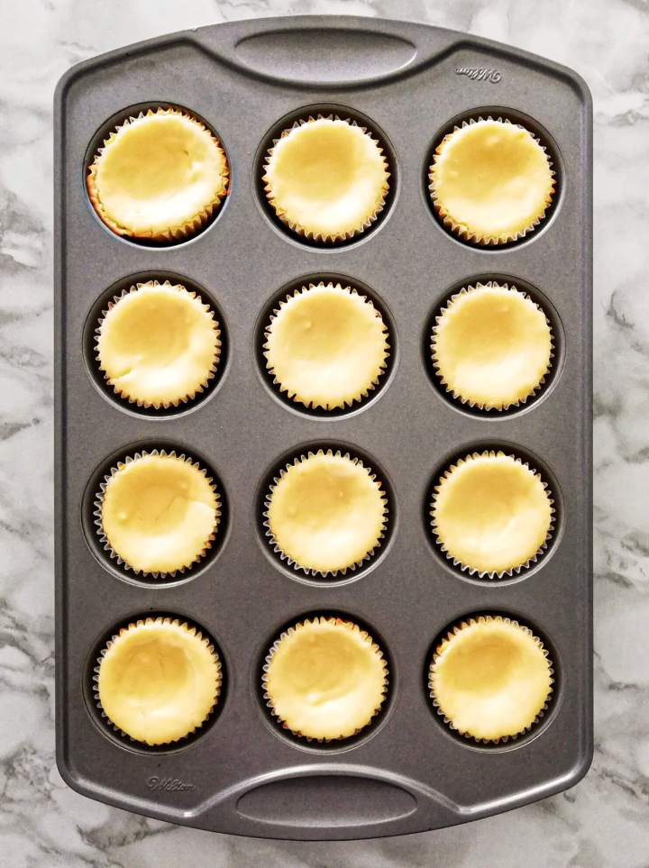mini cheesecakes baked and in muffin tin