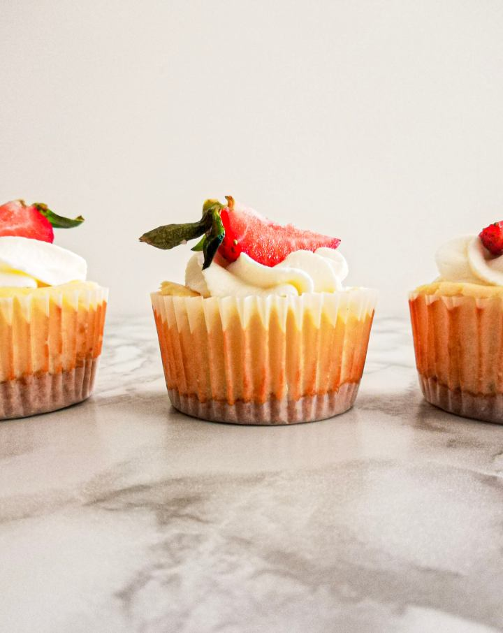 mini cheesecakes topped with whipped cream and strawberries 2