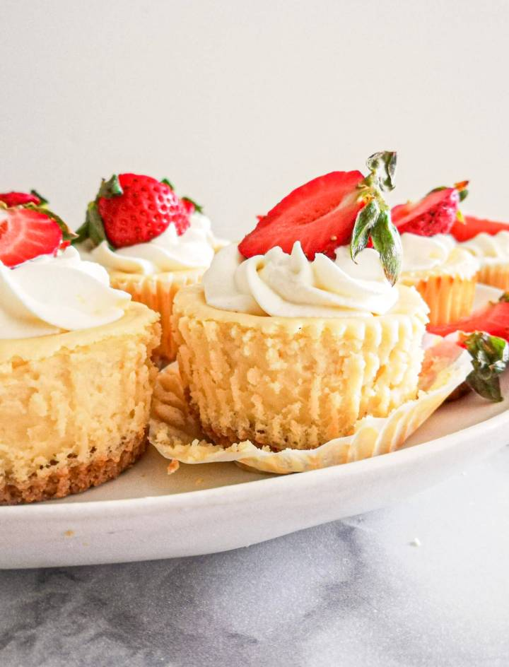 mini cheesecakes topped with whipped cream and strawberries