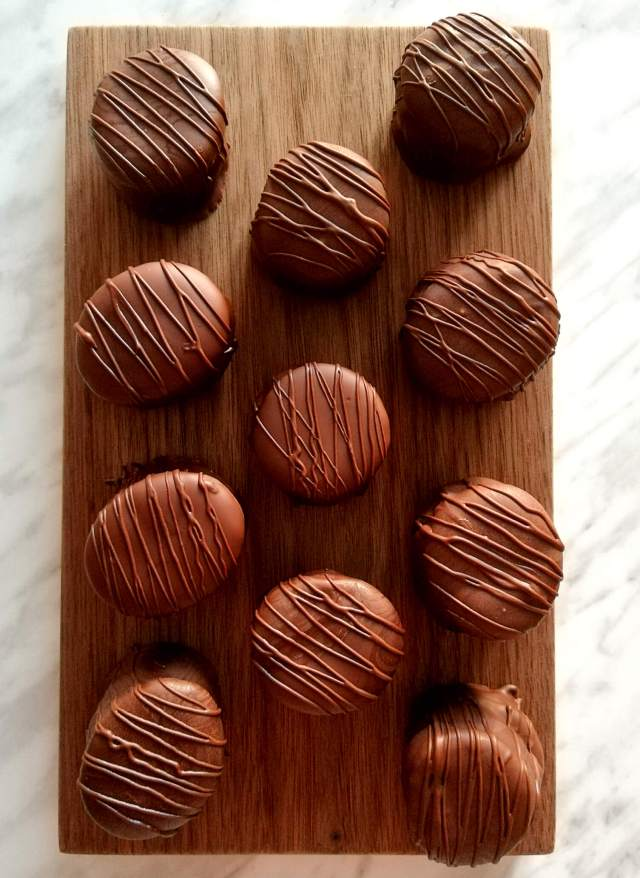 chocolate covered sandwich cookies on wood board