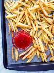 oven french fries on baking sheet with ketchup