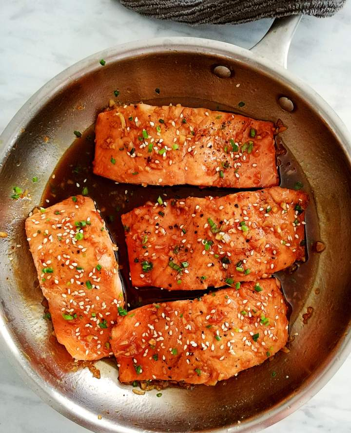 honey garlic salmon in skillet topped with sesame seeds and chives