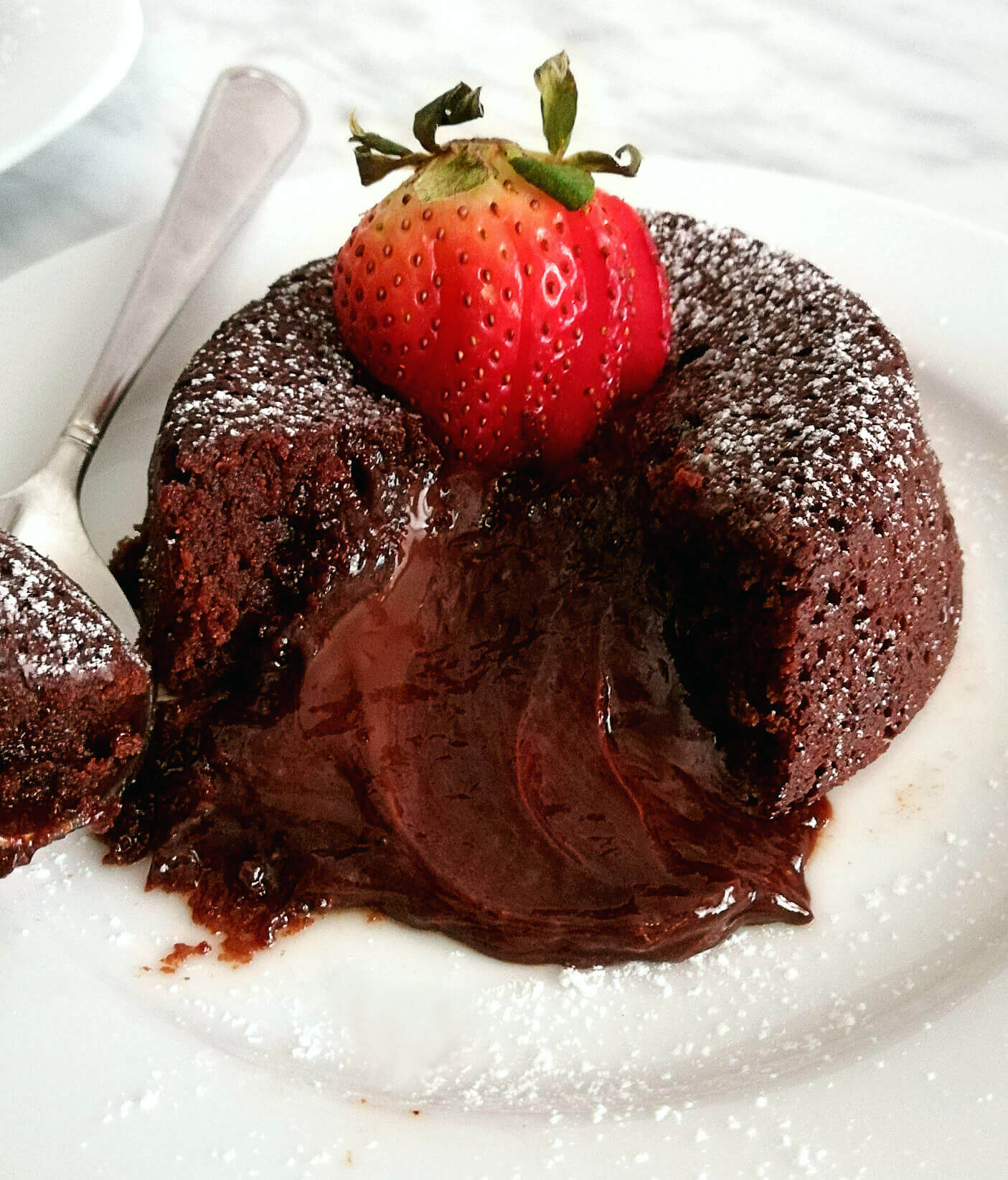 chocolate lava cake dusted with powdered sugar and topped with strawberries (1)