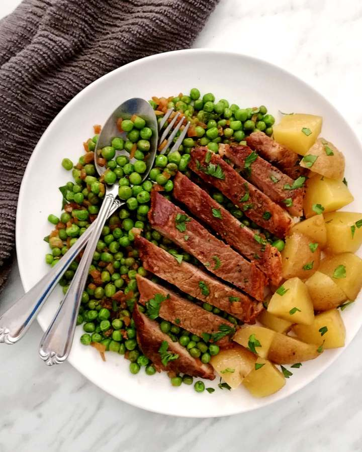 steak and peas with potatoes on side with spoon and fork overhead (1)