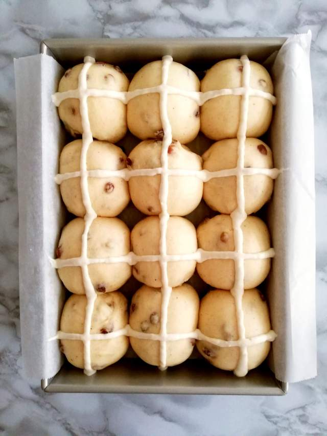 Easter hot cross buns cross piped on overhead view