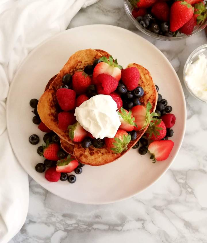 French toast topped with berries and whipped cream overhead