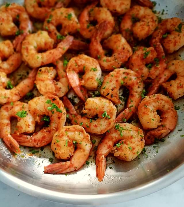 spicy shrimp in skillet topped with parsley close up