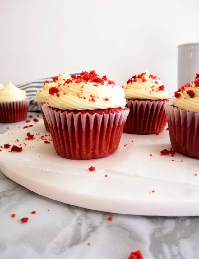 red velvet cupcakes on serving tray topped with frosting and cake crumbs