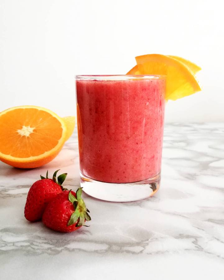 strawberry banana smoothie in cup with orange slices on rim