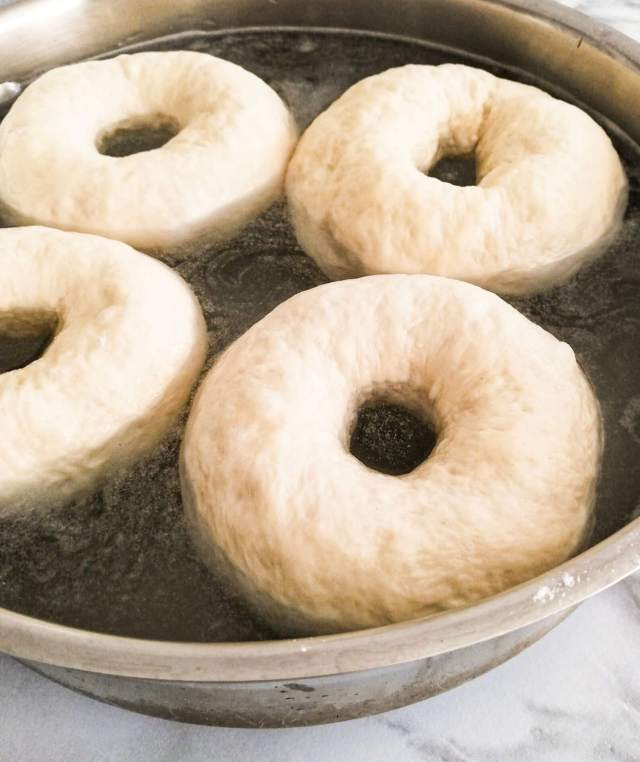 homemade bagels boiling in pot