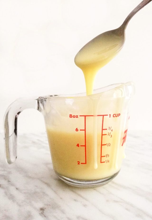 homemade sweetened condensed milk spooning into measuring cup (1)