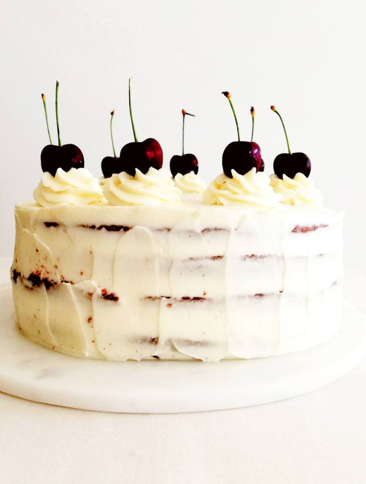 black forest cake frosted and topped with cherries
