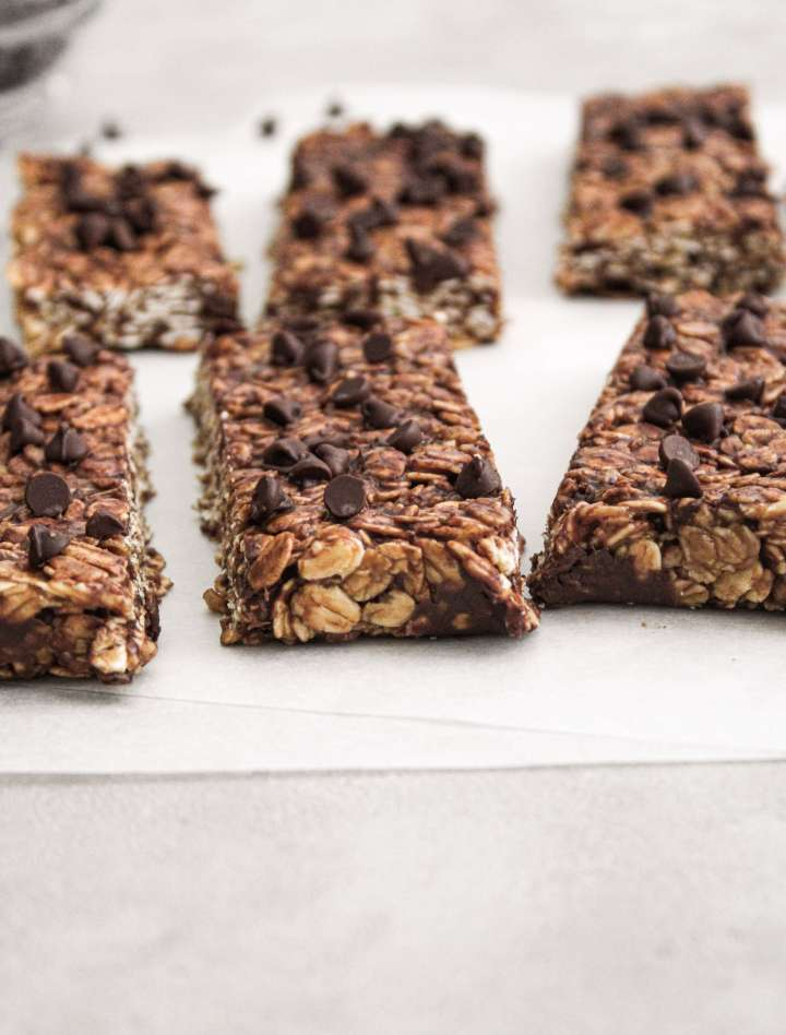 cut chocolate chip oat bars on parchment paper side view
