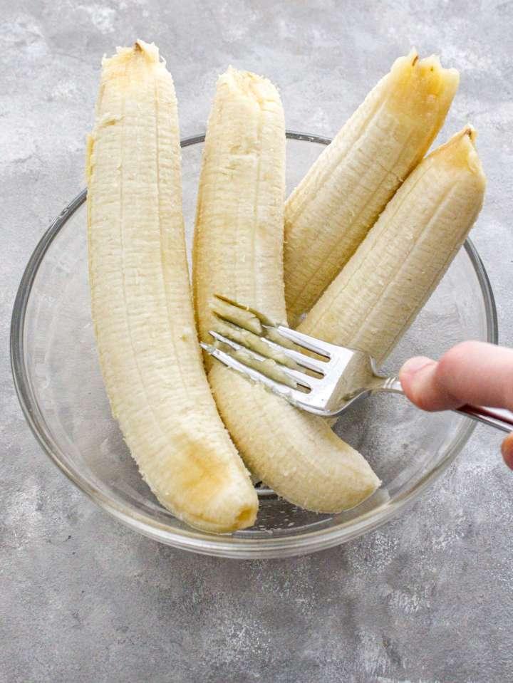 banana bread mashing bananas in bowl