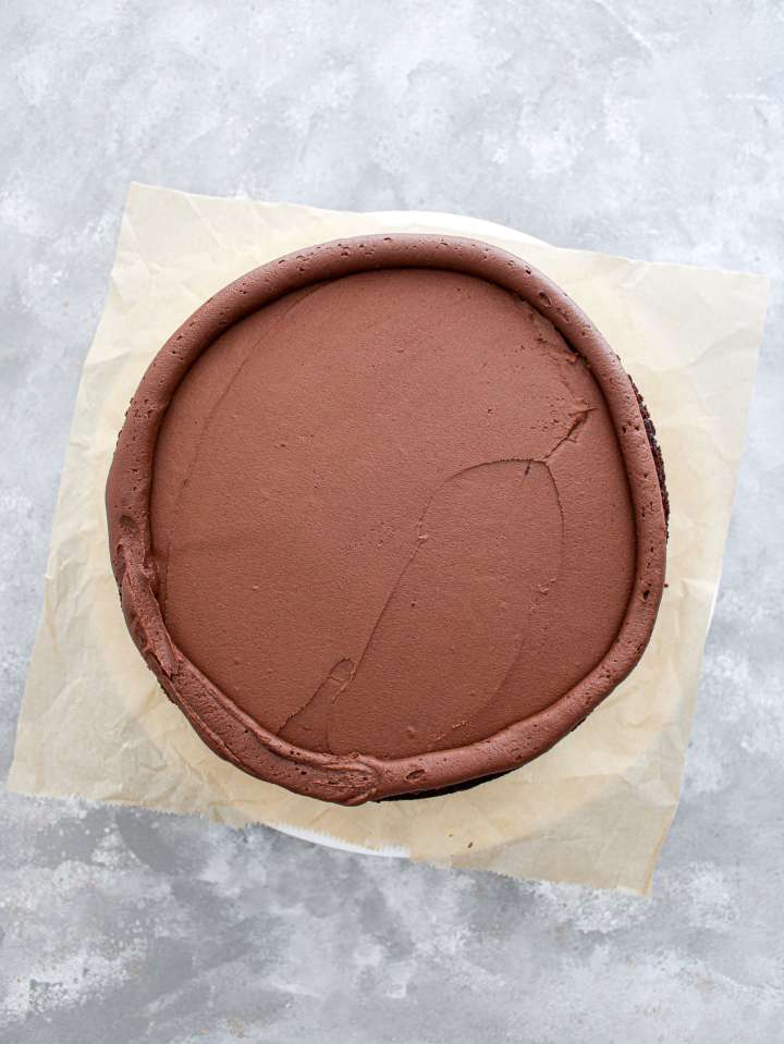 chocolate covered strawberry cake froting spread on first cake layer
