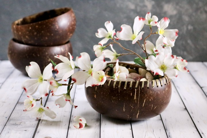 A coconut shell bowl being used to display decorative rocks and artificial flowers.