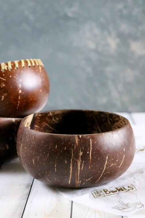A coconut shell bowl laying on Rainforest Bowl branded gift paper with two bowls stacked in the background.