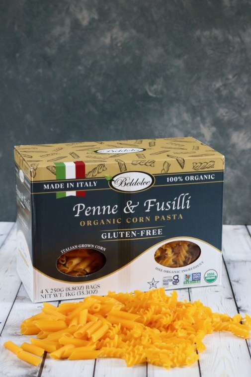 Beldolce gluten free pasta box with a mixture of uncooked penne and fusilli pasta in front of it.