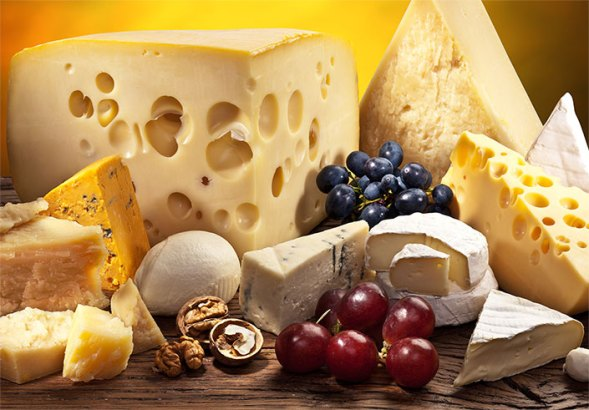 Different kinds of yellow and white cheeses on a brown platter with purple grapes and nuts