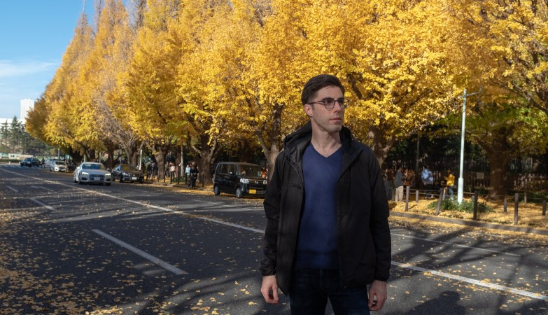 Josh wearing Baubax jacket with bright yellow leaves on trees in the background