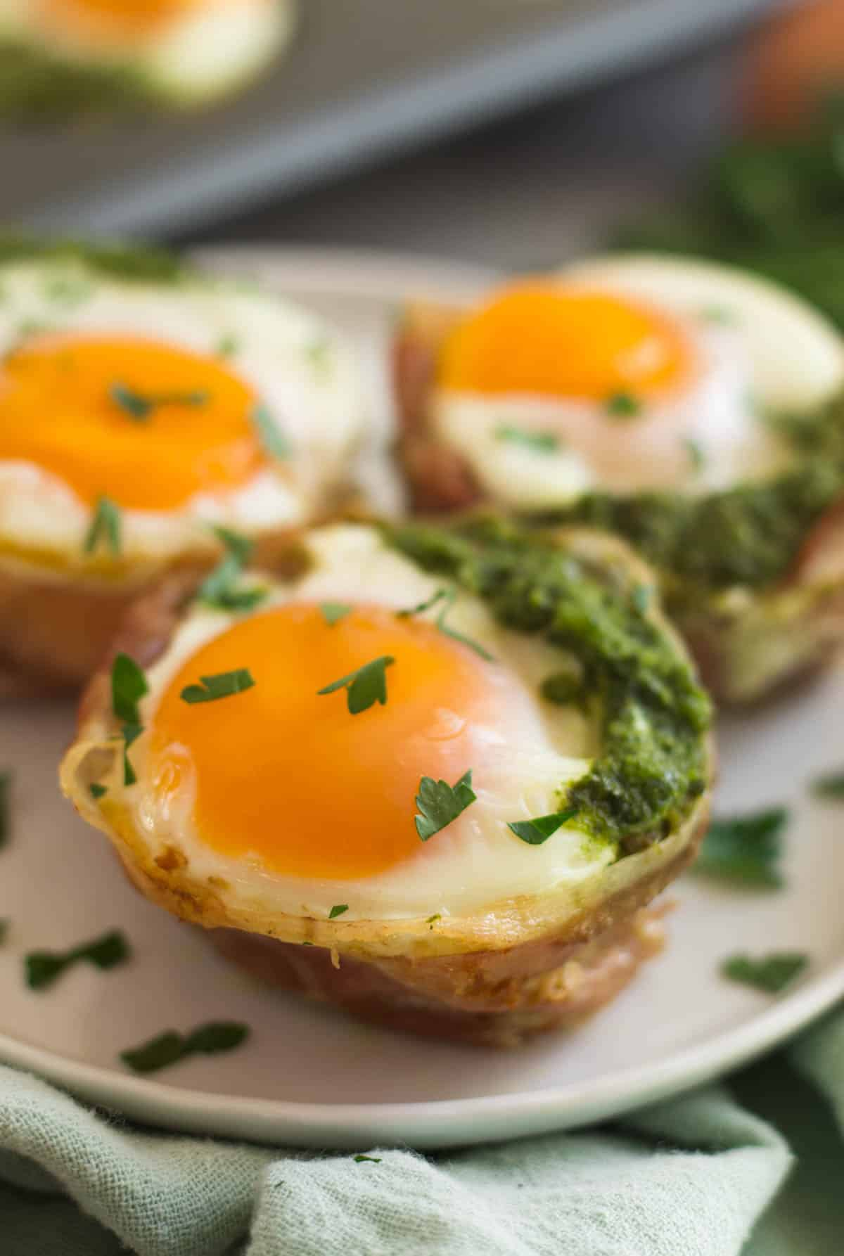 Close up of 3 prosciutto egg cups on a white plate