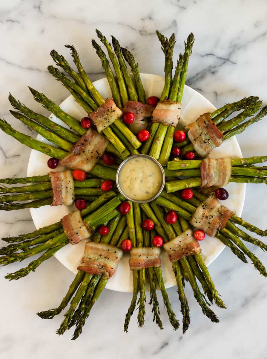 Fun and festive paleo & Whole30 dish with only a few ingredients, a Bacon Wrapped Asparagus Wreath make the perfect appetizer or side at holiday gatherings! - Eat the Gains