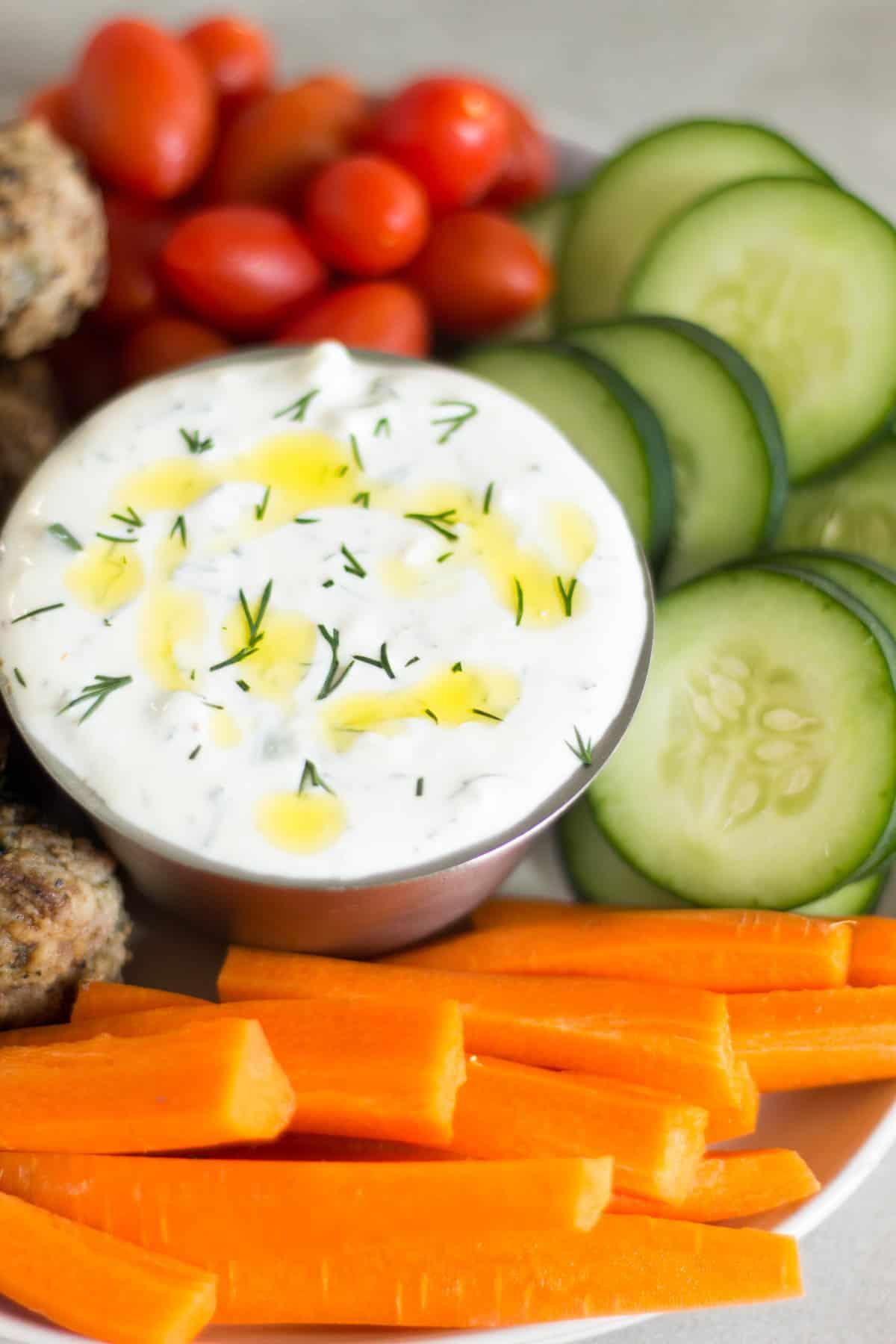 Close up of a bowl of tzatziki sauce with fresh raw veggies around it