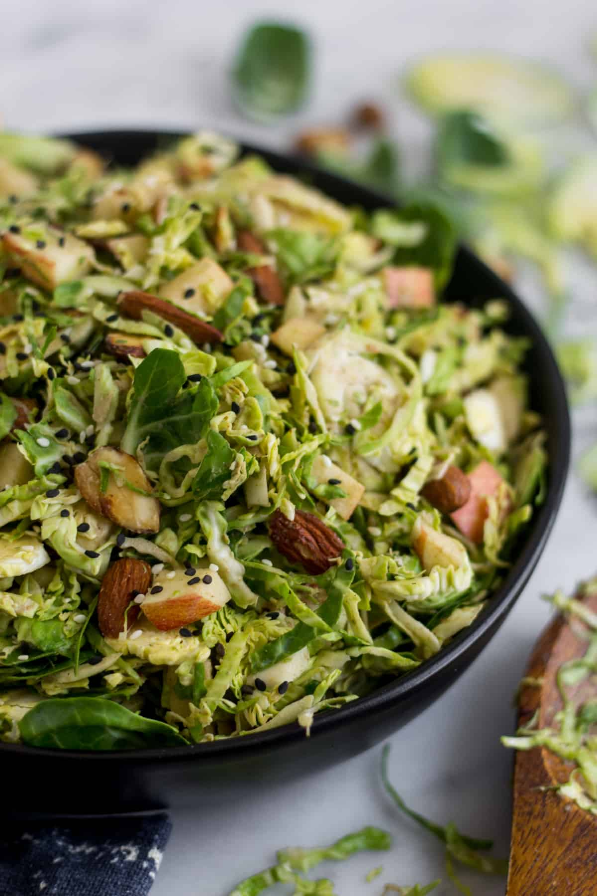 Close up of a black bowl with apple & shaved brussels sprouts salad with a wooden salad tong next to it