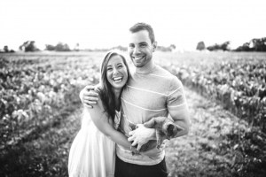 black-and-white-image-of-young-smiling-couple-with-cat-in-field