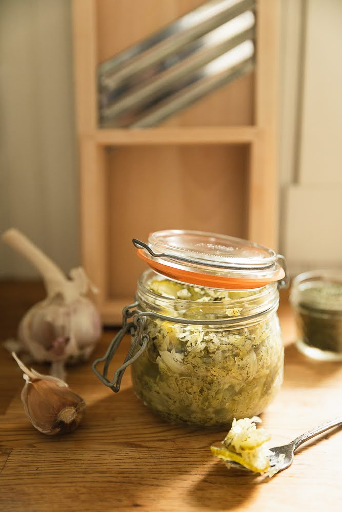sauerkraut in a le parfait jar with garlic and dill around it. Wooden cabbage shredder in the background.