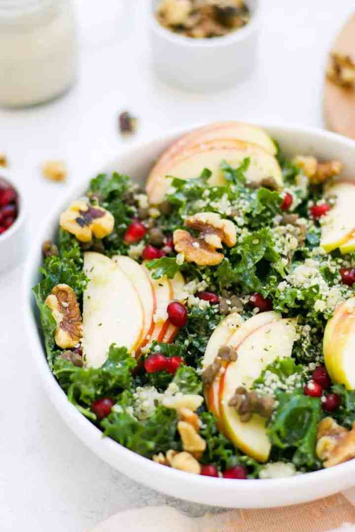 Side view of kale salad with thinly sliced apples.