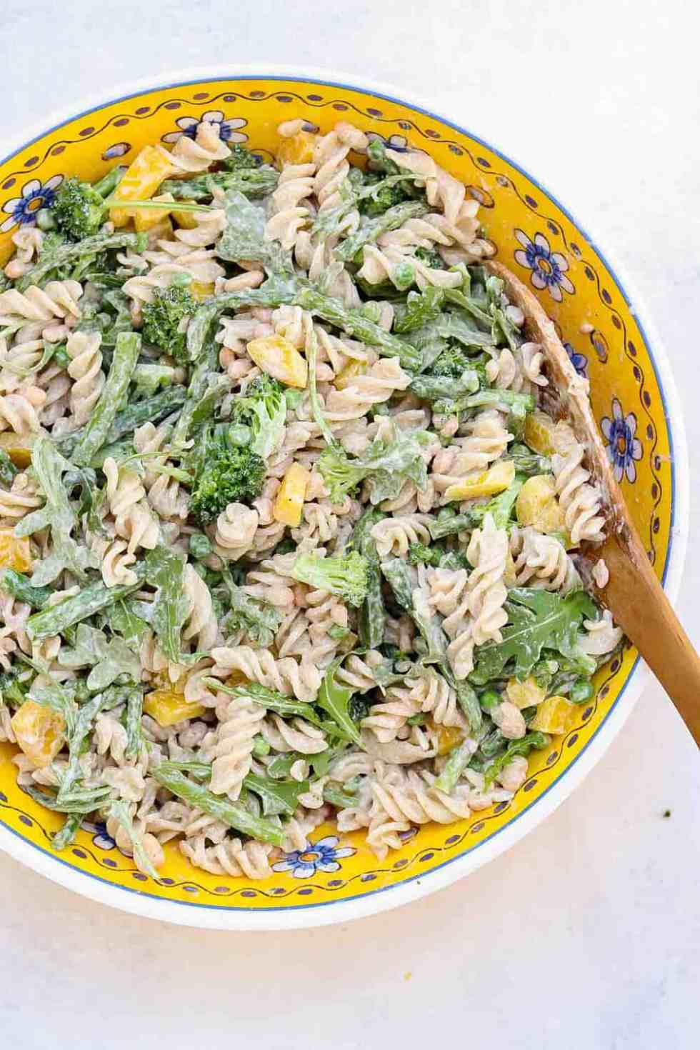 Large yellow bowl filled with this creamy pasta salad with a wooden spoon.