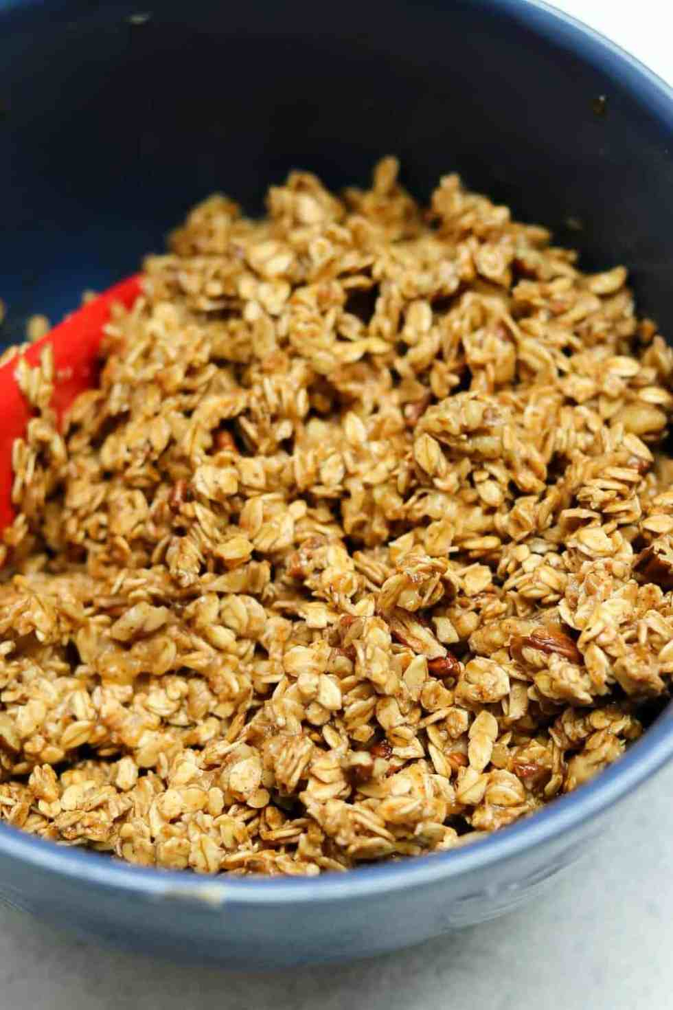 Up close shot of the granola mixture in a large blue bowl.