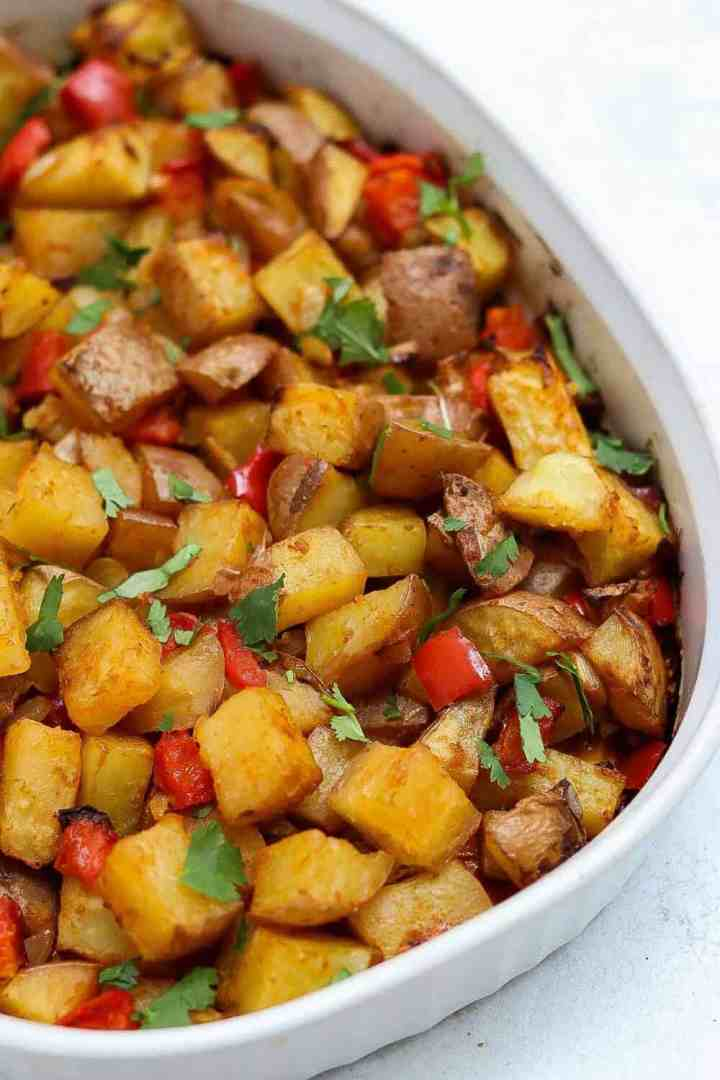 Roasted potatoes with cilantro on top in a white dish.
