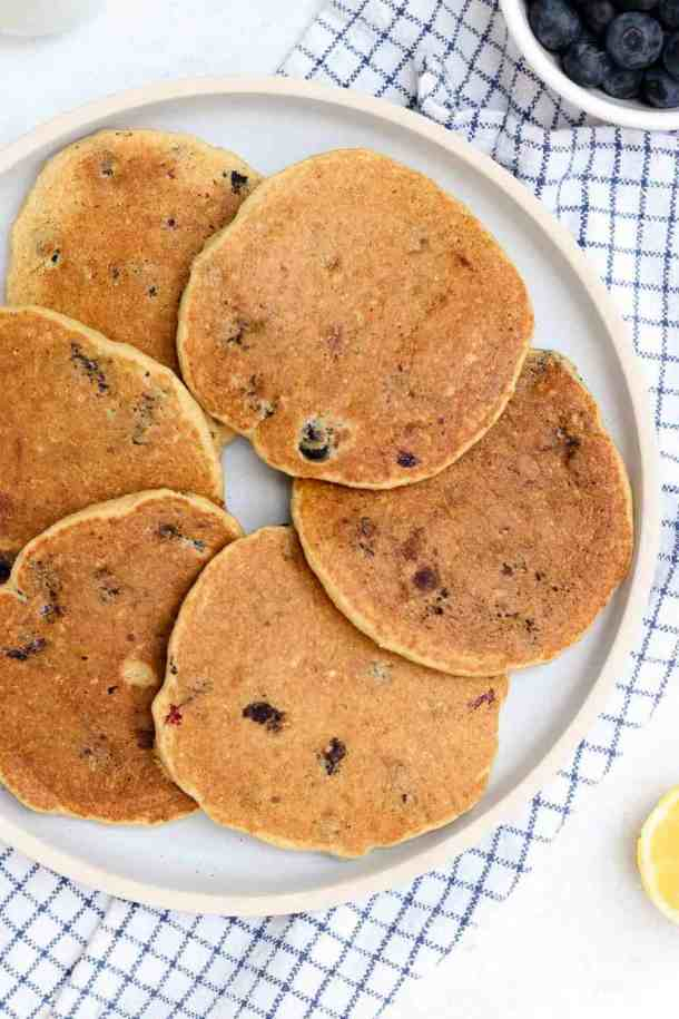 Six lemon blueberry pancakes arranged in a circle on a blue plate.