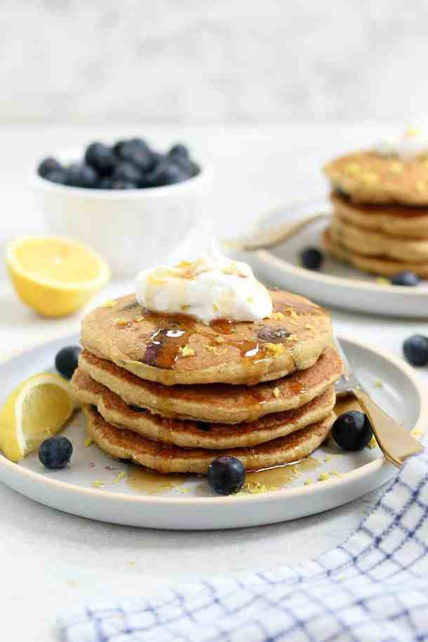 Four lemon blueberry pancakes stacked on a plate with coconut whipped cream on top.