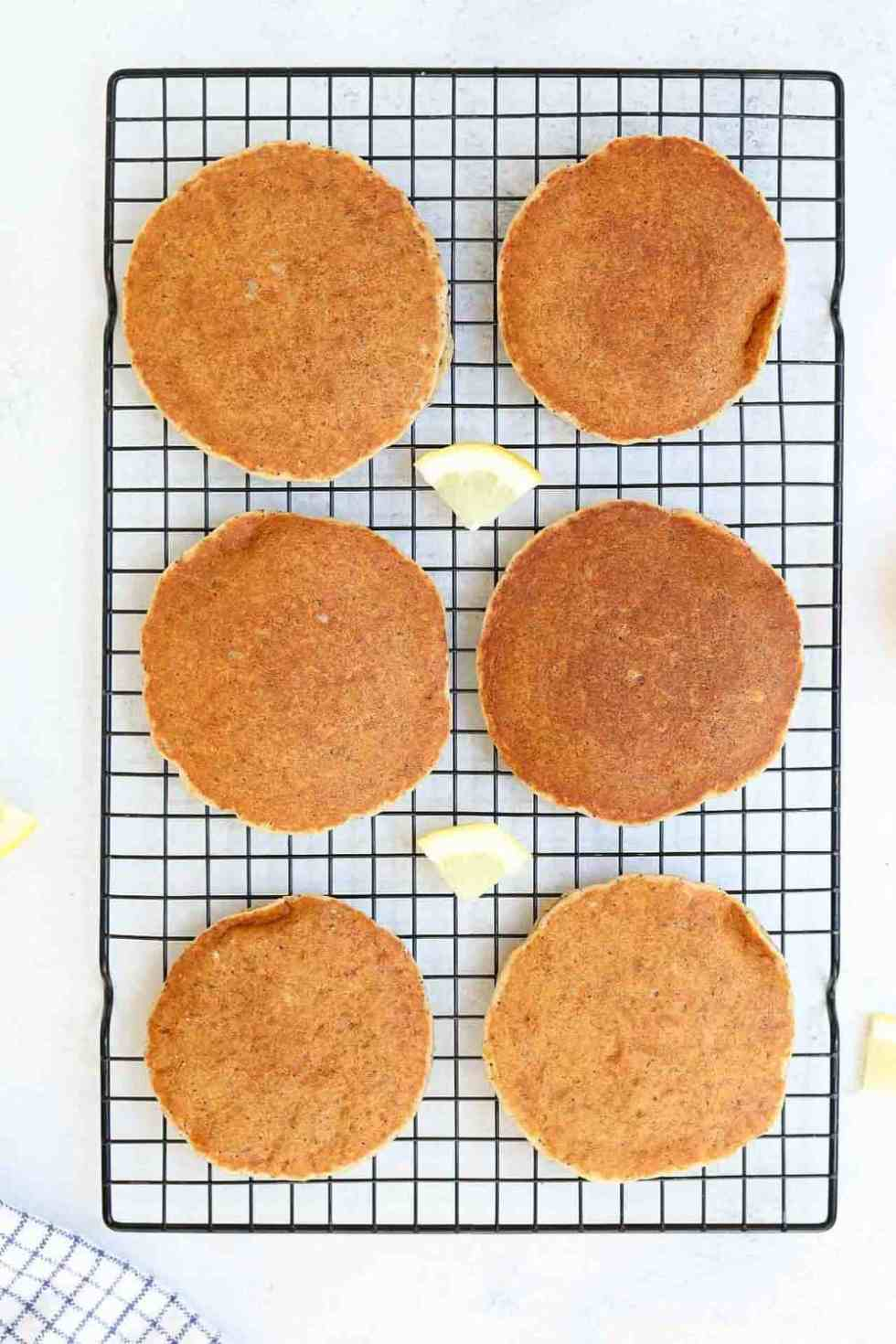 Six pancakes lined up on a black baking tray with lemon wedges.