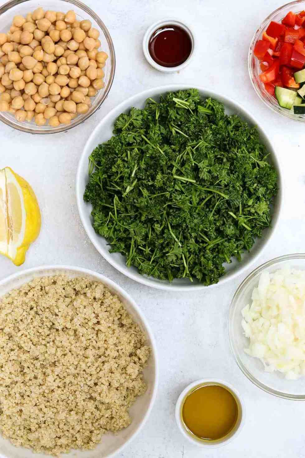 Ingredients lined up in white and clear bowls for the quinoa tabbouleh salad.