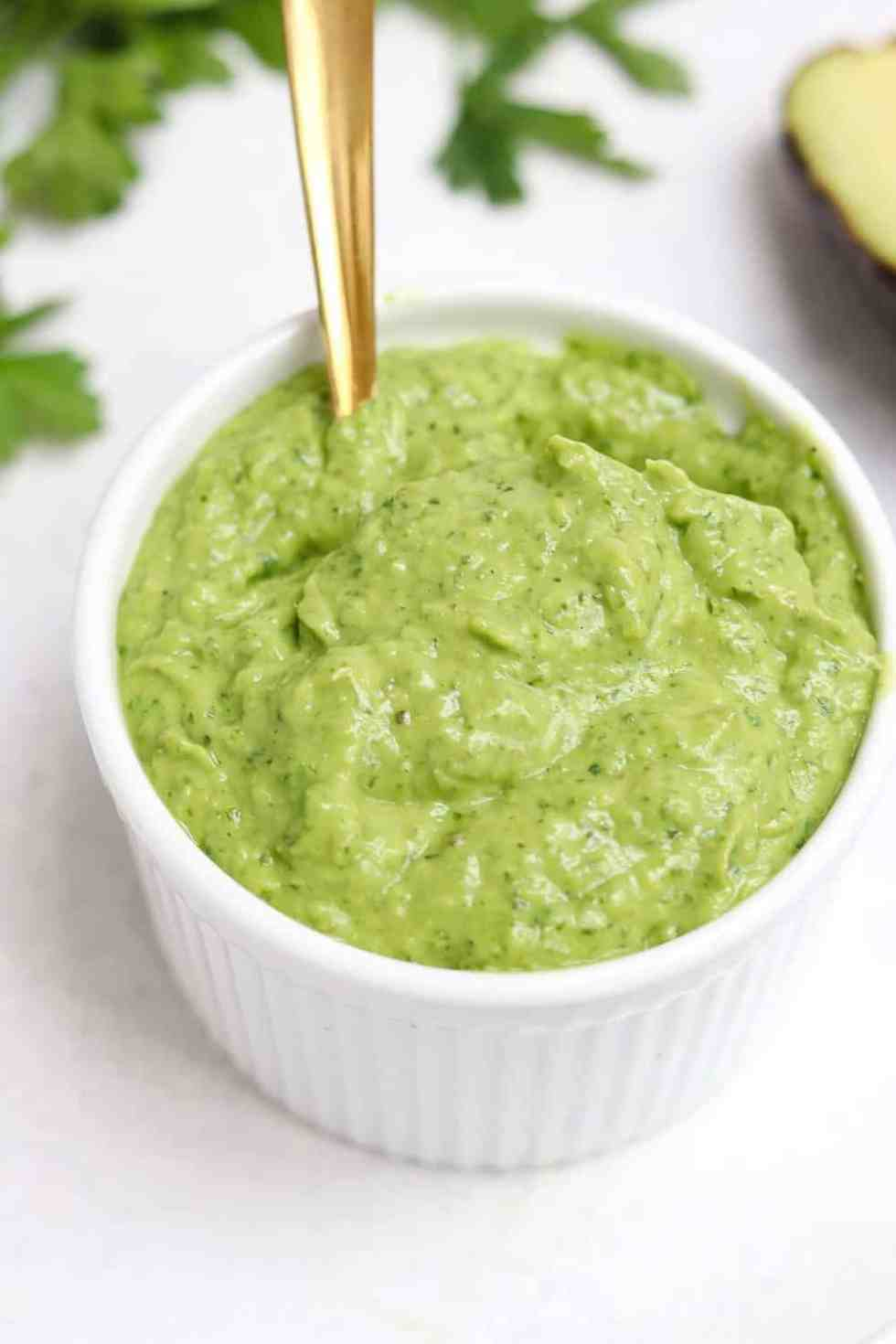 Up close of green goddess dressing in a small white ramekin.