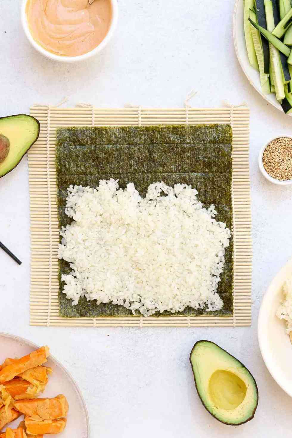 Sushi nori with white rice on top of a bamboo rolling mat.