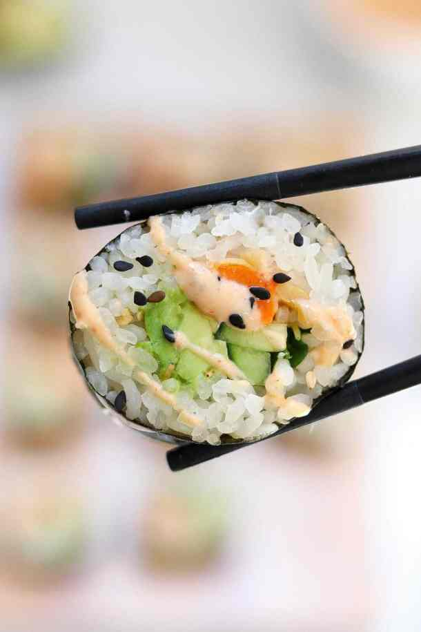 Up close image of vegetarian sushi recipe with black chopsticks holding it up.