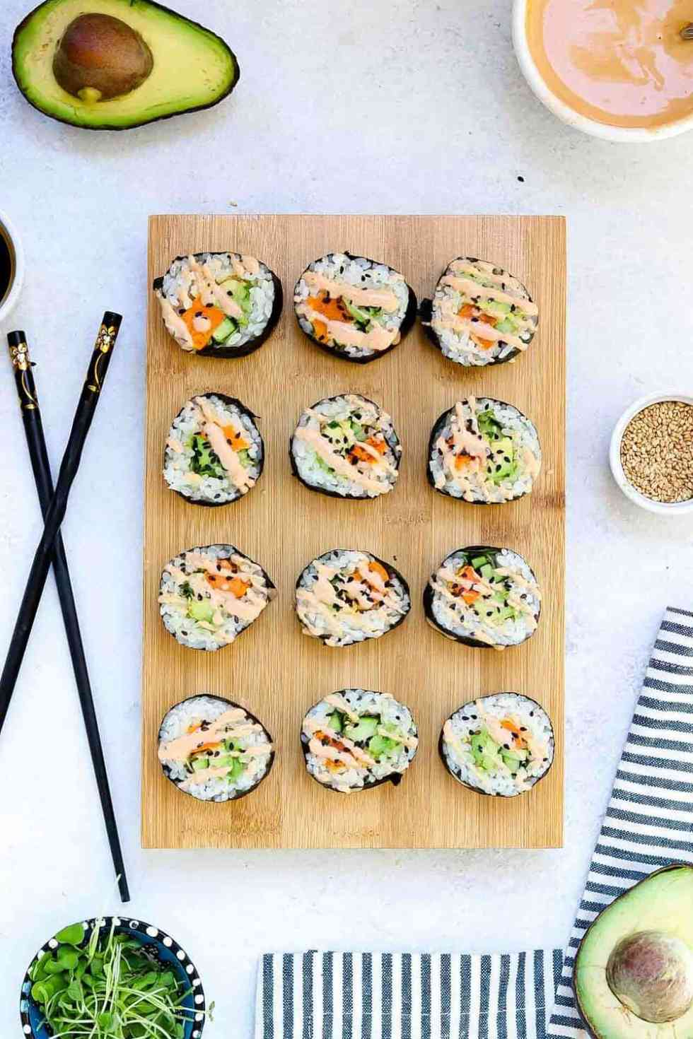 12 sushi rolls lined up on a wooden board with black chopsticks and a tahini drizzle.