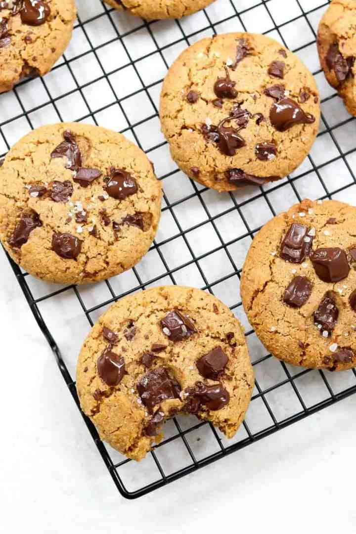 Cookies with melted chocolate fresh out of the oven on a black drying rack.