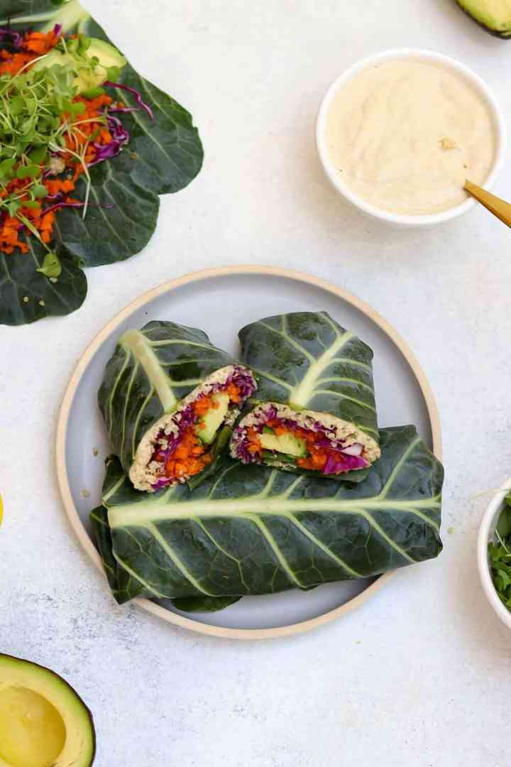 Two collard wraps on a blue plate with tahini dressing in the back.